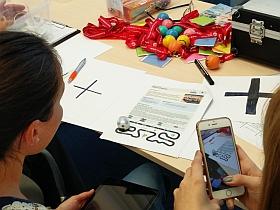 Ozobot Roboter mit gezeichnetem Programm wird mit Smartphone gefilmt.
