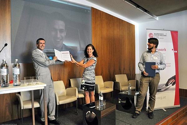 Andreas Grimmer ist via Skype zugeschaltet und erhält die Preisurkunde von Wilfried Seyruck und Christine Wahlmüller-Schiller