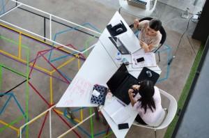 Zwei junge Frauen arbeiten mit Laptops